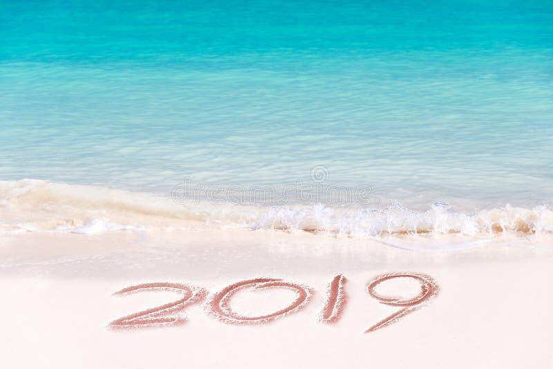 2019 som är skriftlig på sanden av en strand, reser begrepp för nytt år royaltyfri foto