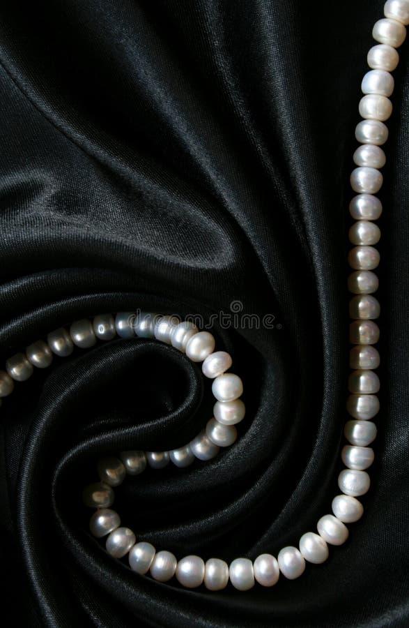 som bakgrund pryder med pärlor black silk white arkivfoton