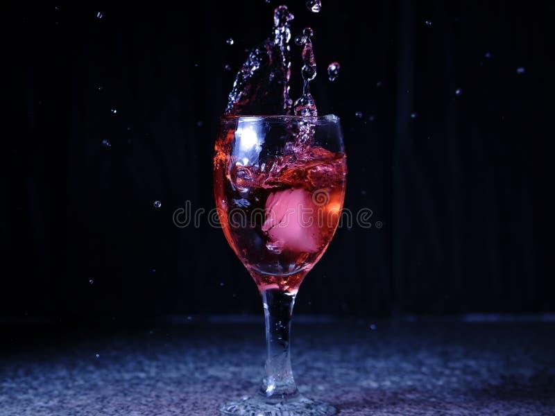 Is som faller på ett exponeringsglas med drinken som spill och färgstänk arkivfoto