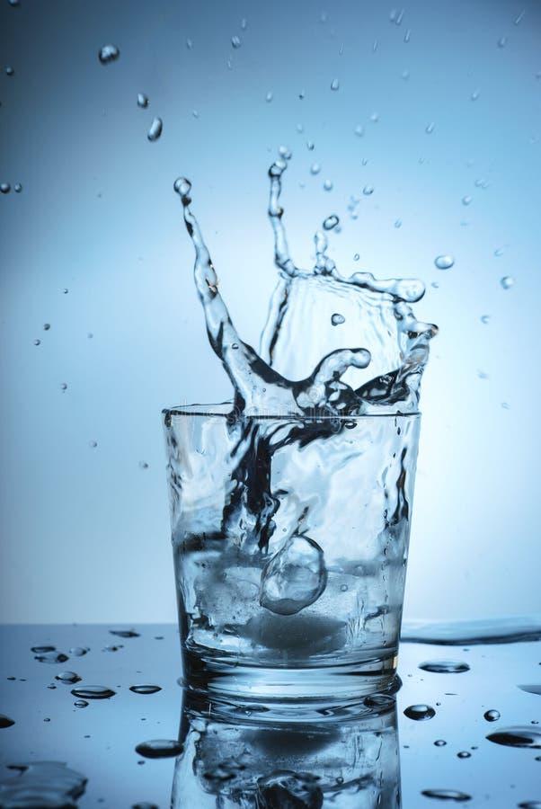Is som plaskar i ett kallt exponeringsglas av vatten arkivbild