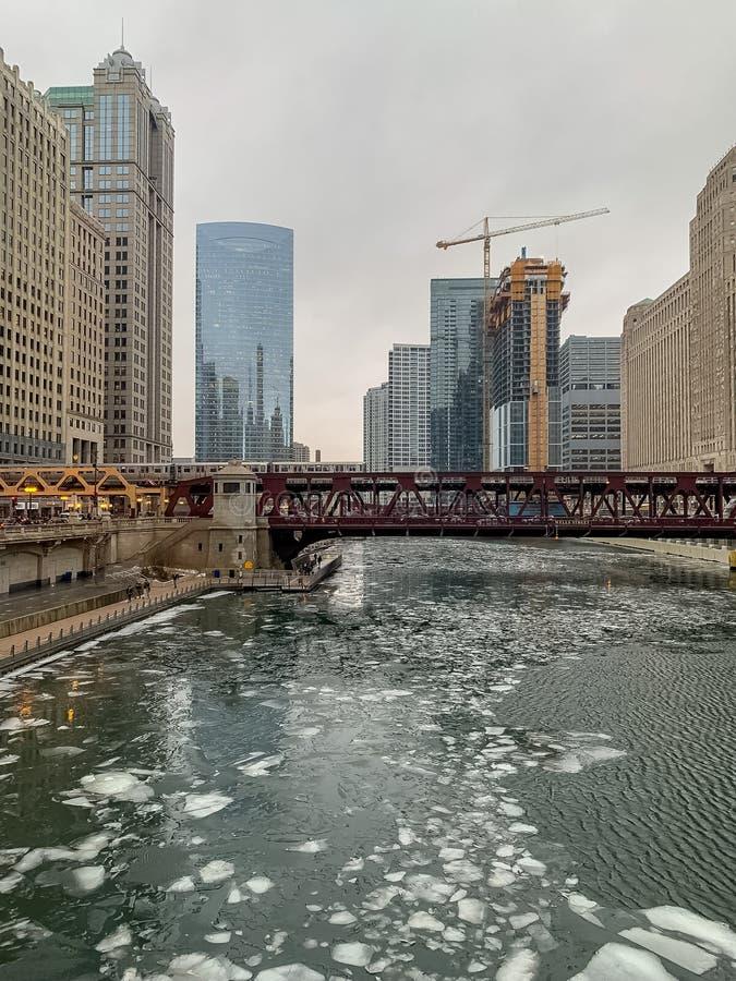 Is som svävar på Chicagoet River, medan el-drevet korsar över på brunngatan royaltyfria foton