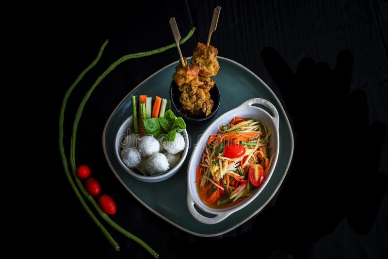Som Tam Thai - Thai Green Papaya Salad. With chicken satay sticky rice and vegetable stock images
