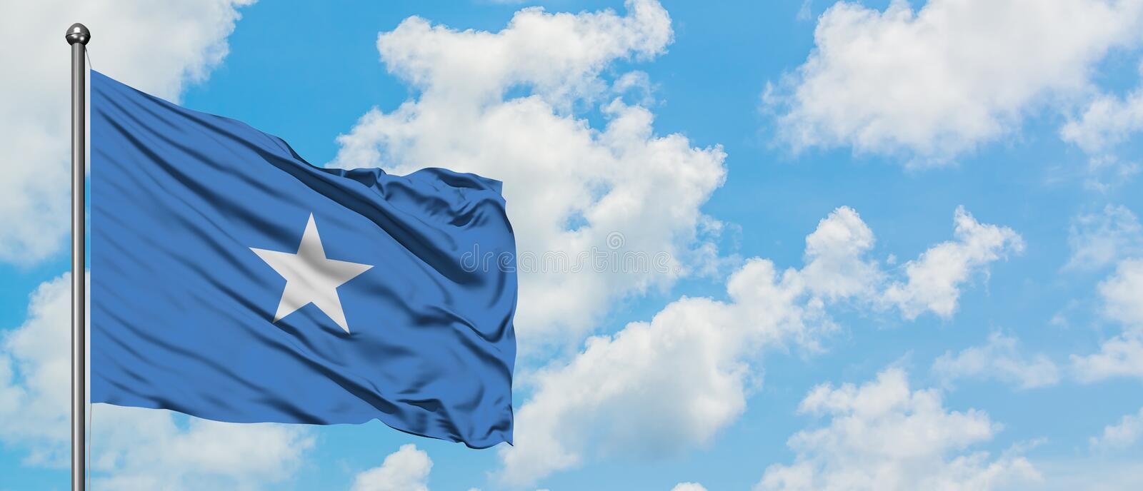Somalia flag waving in the wind against white cloudy blue sky. Diplomacy concept, international relations.  royalty free stock image