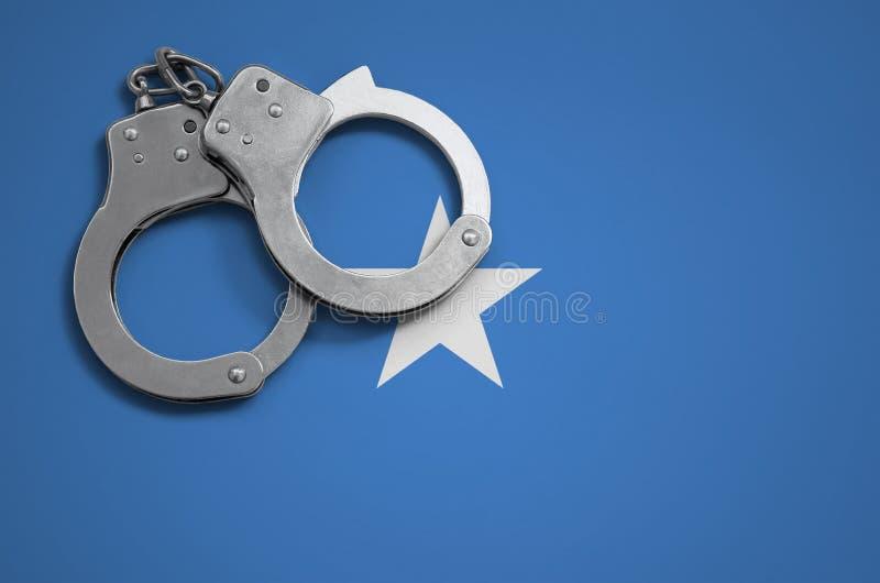 Somalia flagga- och polishandbojor Begreppet av brottet och anstötar i landet royaltyfri foto