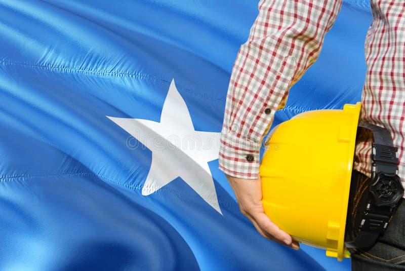 Somalian inżynier trzyma żółtego zbawczego hełm z machać Somalia chorągwianego tło Budowy i budynku poj?cie zdjęcie royalty free