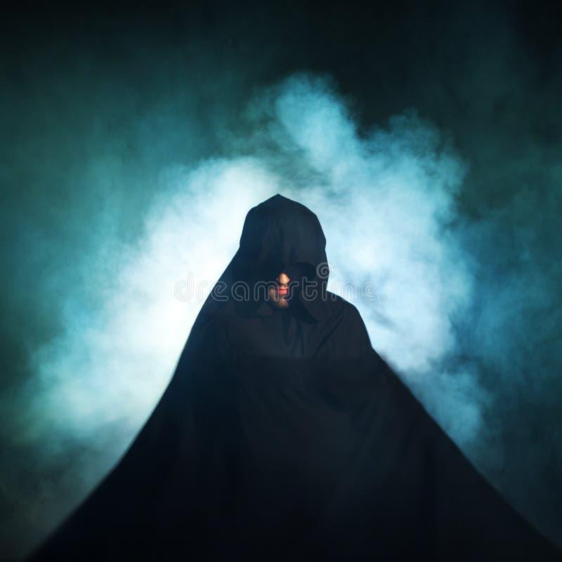 Somber beeld Mens in een zwarte mantel Duivels beeld Tovenaarillusionist stock afbeelding