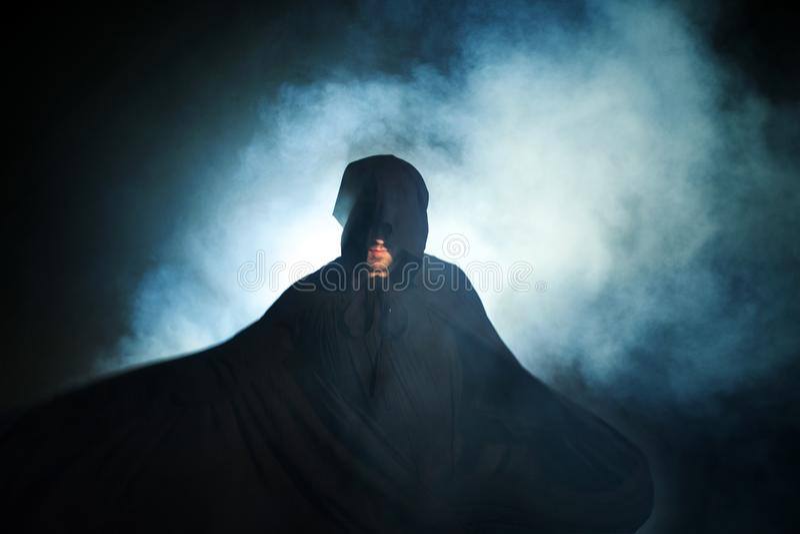 Somber beeld Mens in een zwarte mantel Duivels beeld Tovenaarillusionist stock fotografie