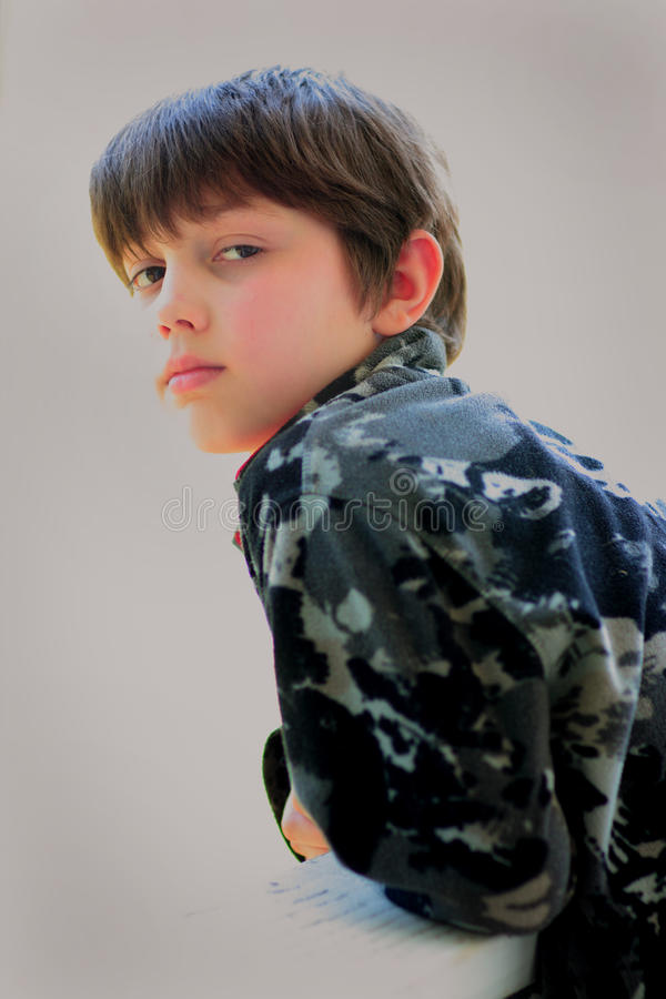 Somber Young Dark Haired Boy stock photo
