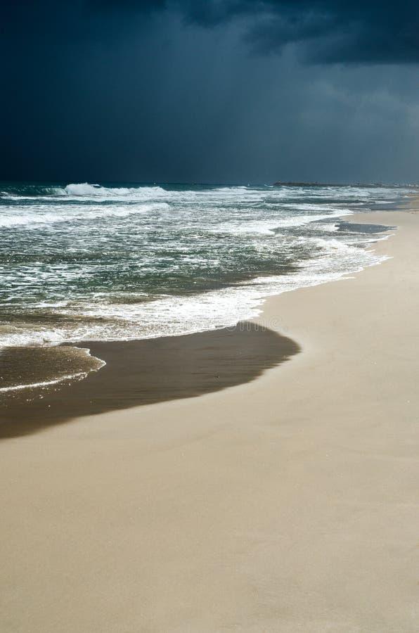 Sombere donkere bewolkte hemel, wilde overzeese golven Leeg donker strand vlak vóór de wilde regenval stock afbeeldingen