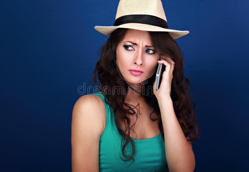 Sombere ongelukkige frustratievrouw in de zomerhoed die op mobiel spreken royalty-vrije stock afbeeldingen