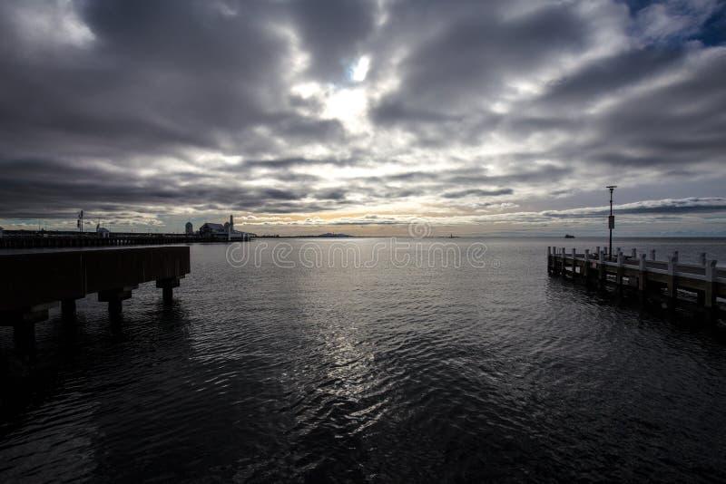 Sombere zware regenwolken die binnen van de horizon, rust vóór onweer rollen Geelongstrand, Australië royalty-vrije stock foto's