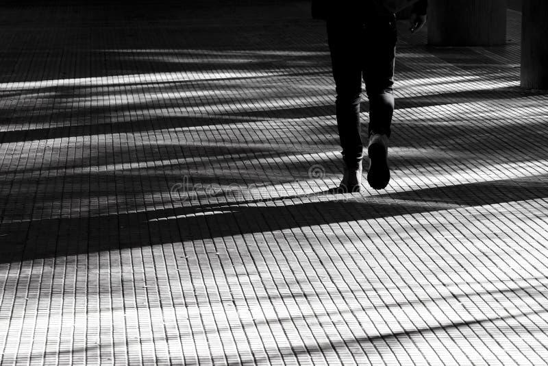 Sombra borrosa de la silueta de una persona que camina en una calzada de la arcada de la ciudad fotos de archivo libres de regalías