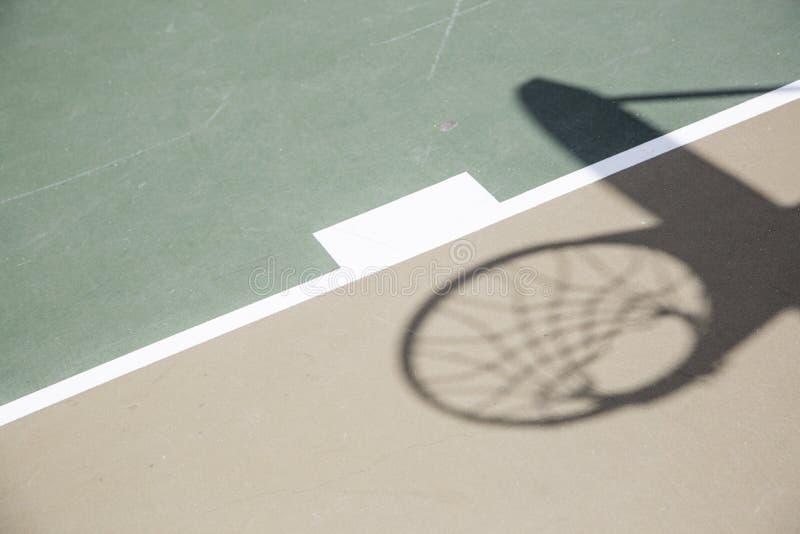 Sombra da aro e da rede de basquetebol contra a corte fotografia de stock