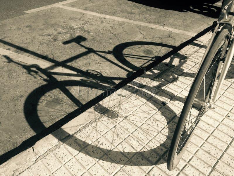 Download Sombra Da Bicicleta Estacionada Sobre A Estrada Asfaltada Foto de Stock - Imagem de veículo, cena: 65576358