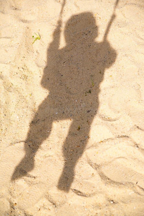 Sombra da criança no balanço foto de stock