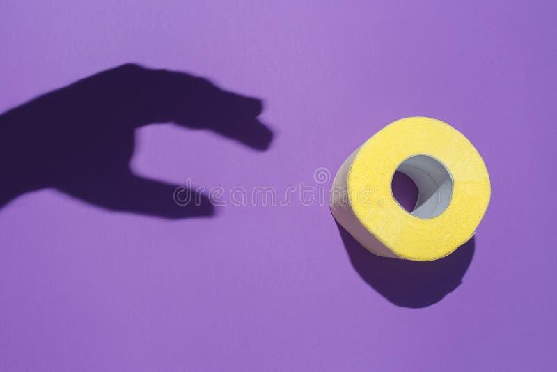 A sombra da mão alcança para o papel higiênico amarelo no fundo violeta O conceito da higiene, introduções da digestão foto de stock royalty free