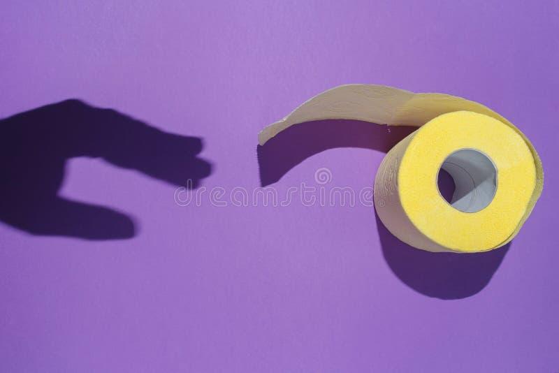 A sombra da mão alcança para o papel higiênico amarelo no fundo violeta O conceito da higiene, introduções da digestão fotos de stock royalty free