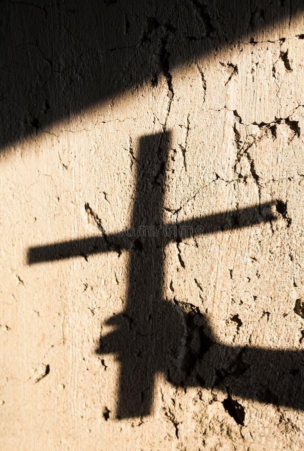 Sombra da mão que guarda uma cruz imagem de stock
