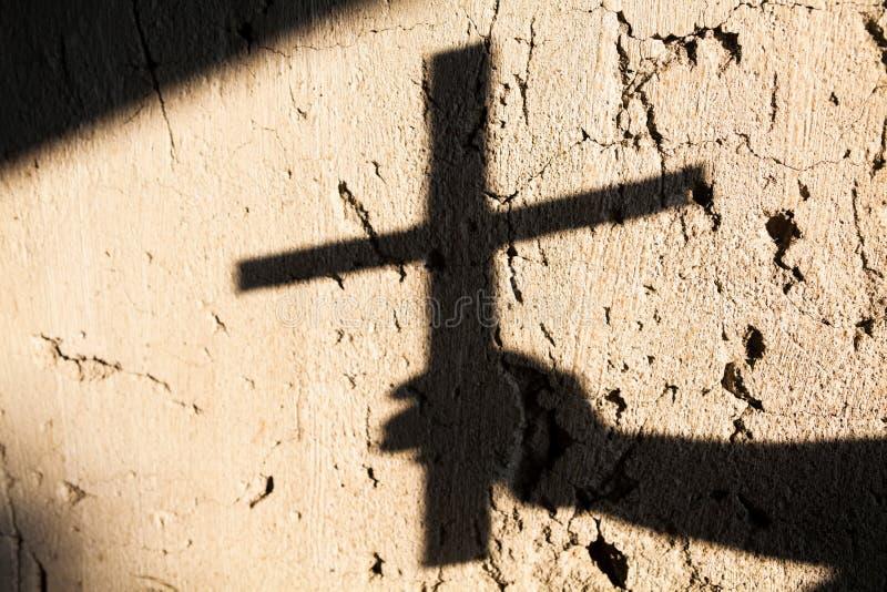 Sombra da mão segurando uma cruz imagem de stock royalty free