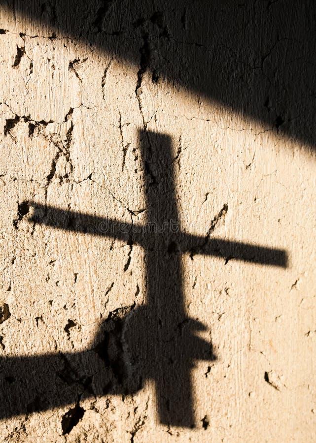 Sombra da mão segurando uma cruz imagem de stock