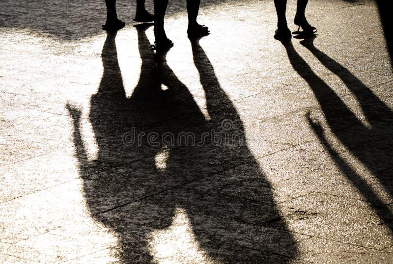 Sombra da reflexão e silhueta obscuras de três pessoas dos pés no passeio brilhante do verão imagem de stock