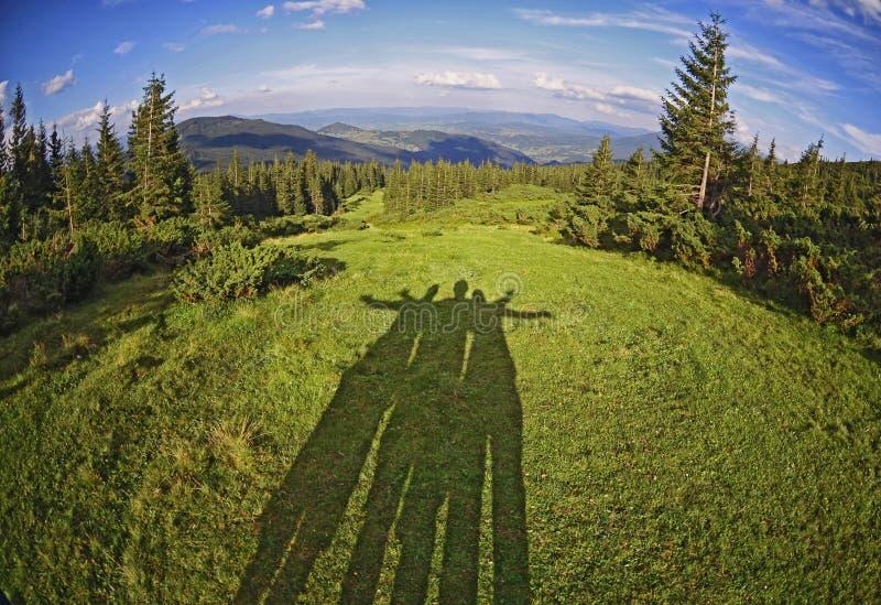 Sombra de amigos entre paisaje fantástico hermoso en el fondo de las montañas cárpatas fotos de archivo