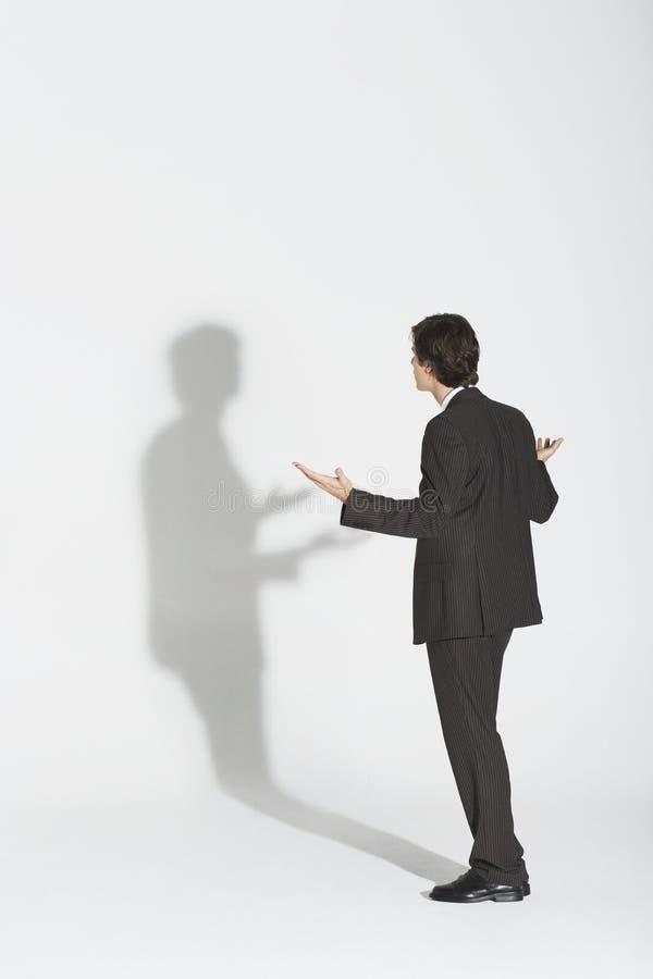 Sombra de Arguing With Own del hombre de negocios fotos de archivo libres de regalías