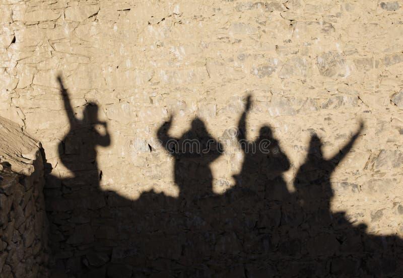 Sombra de cuatro turistas felices en la pared del palacio de Shey fotografía de archivo