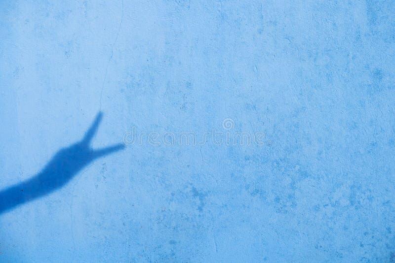 Sombra de dos fingeres para arriba en fondo azul de la pared fotografía de archivo libre de regalías