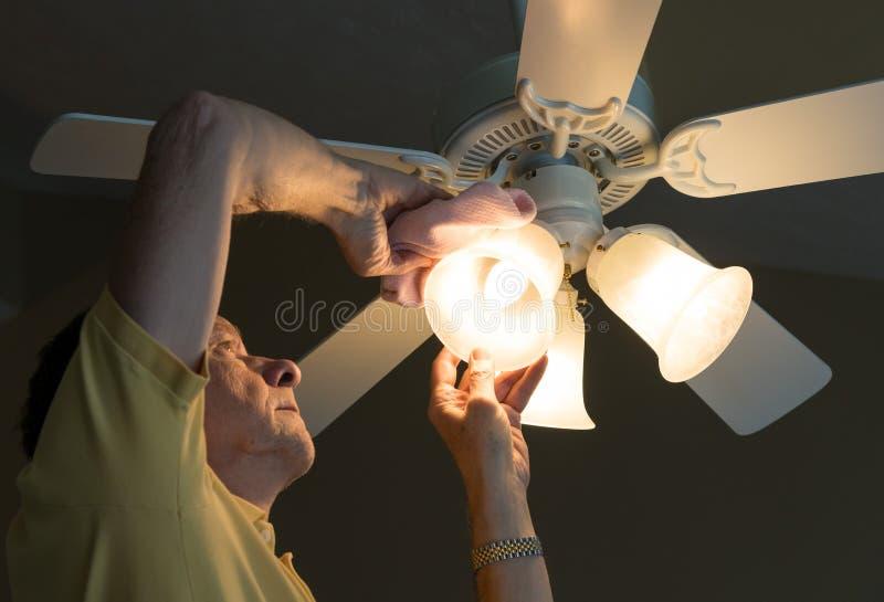 Sombra de lámpara caucásica mayor de polvoreda del hombre en fan y luz de techo fotografía de archivo libre de regalías