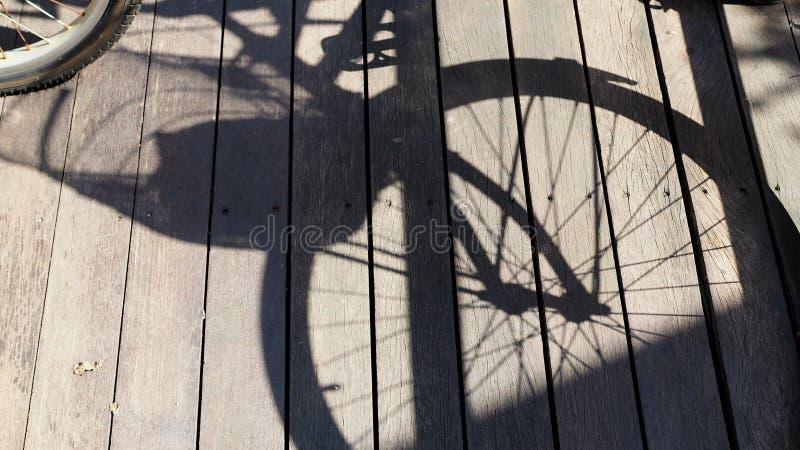 Sombra de la bicicleta en el piso de madera Fondo abstracto de la textura fotografía de archivo