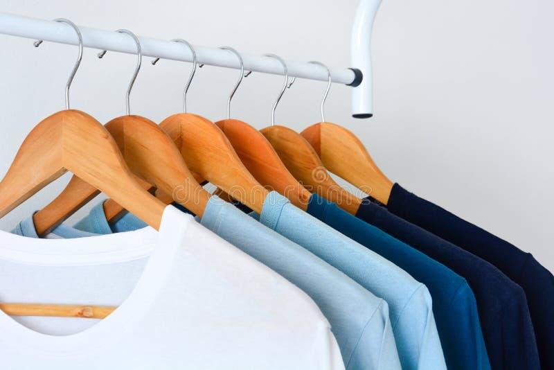Sombra de la colección de las camisetas azules del color de tono que cuelgan en la suspensión de ropa de madera en armario fotografía de archivo