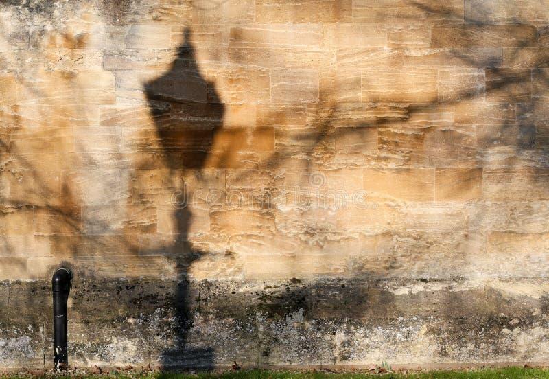 Sombra de la lámpara de calle en vieja textura de la pared de piedra foto de archivo libre de regalías