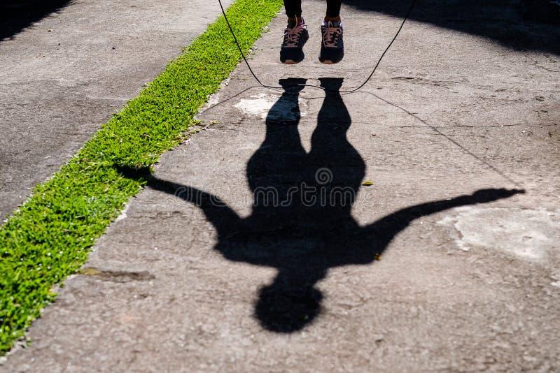 Sombra de la mujer con la cuerda de salto negra de la ropa en el parque imagen de archivo libre de regalías