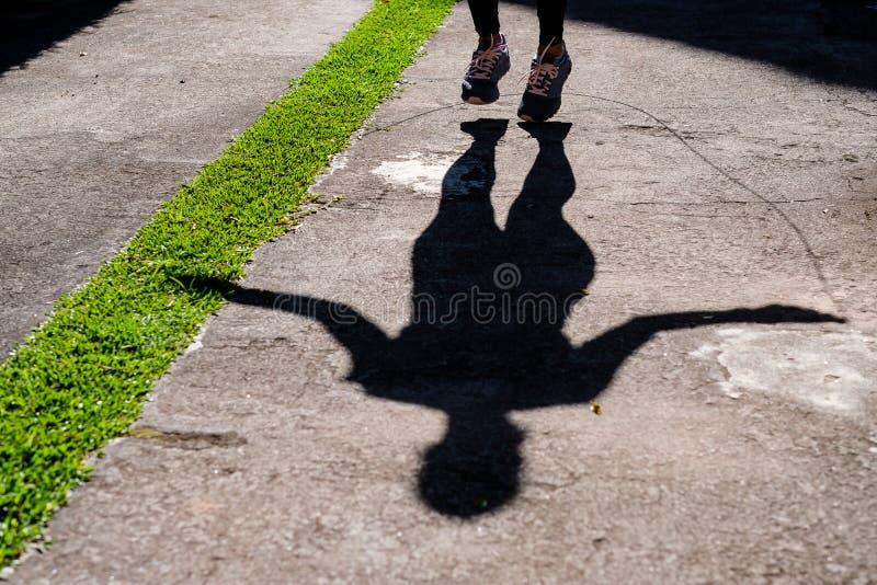 Sombra de la mujer con la cuerda de salto negra de la ropa en el parque fotografía de archivo