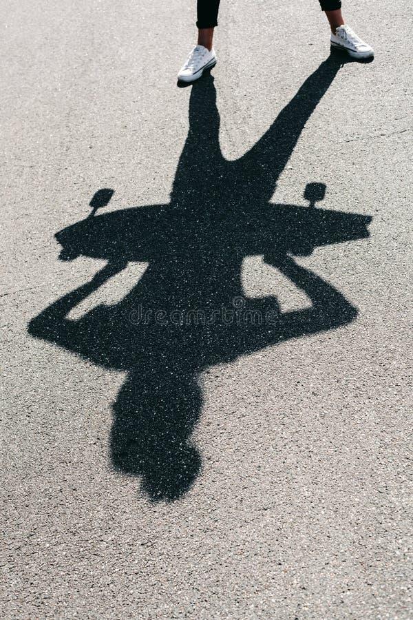 Sombra de la mujer joven que presenta con el monopatín imágenes de archivo libres de regalías