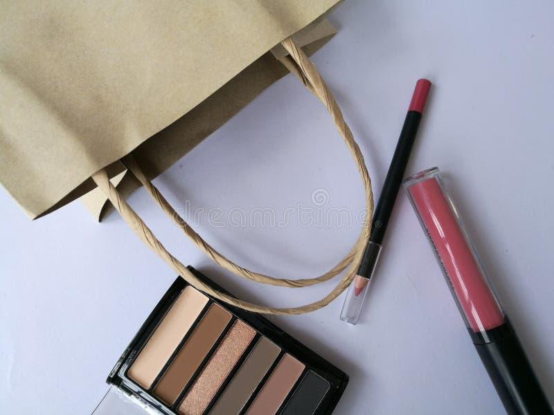 Sombra de ojos cosmética de los productos del maquillaje de la bolsa de papel de Brown, cepillo encendido, tono del trazador de l fotografía de archivo libre de regalías