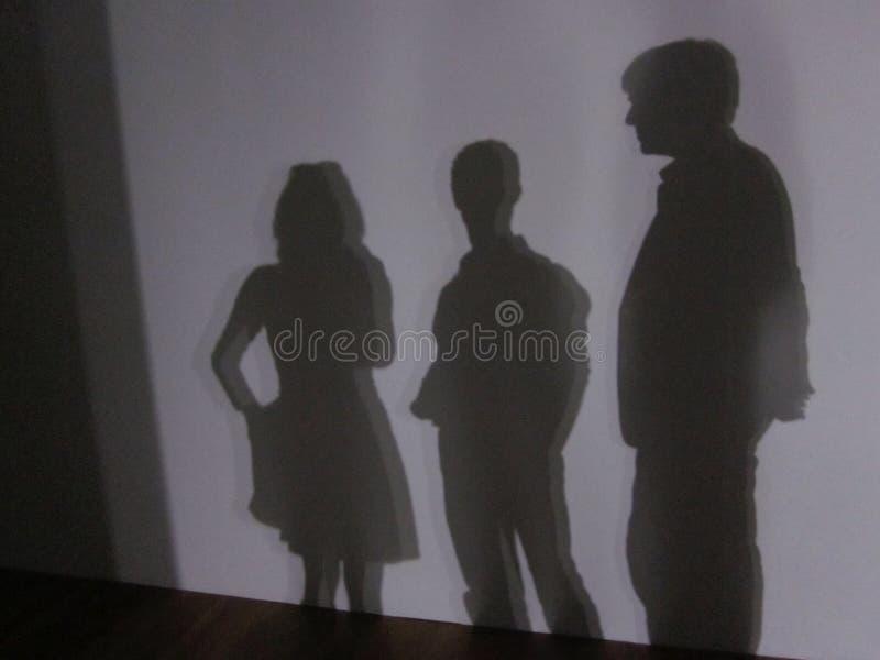 Sombra de três pessoas que estão na frente de uma parede branca imagens de stock