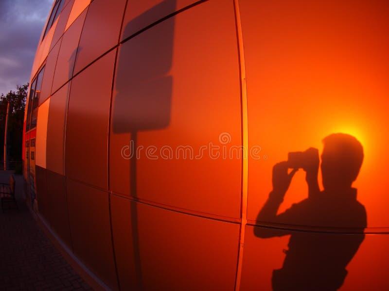 A sombra de um homem em uma parede vermelho-alaranjada, que fotografe uma estrada fotografia de stock