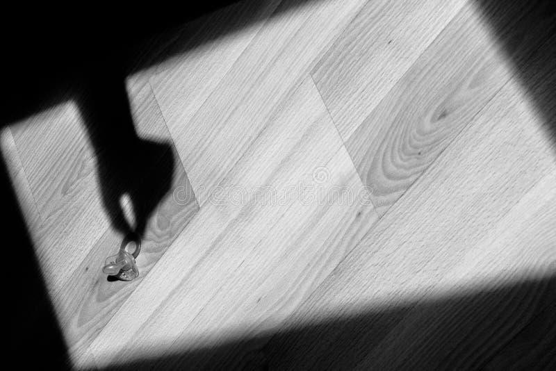 A sombra de uma mão toma uma chupeta do assoalho Arte abstrato, com símbolos das crianças foto de stock