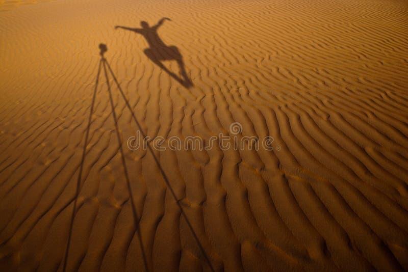 Sombra de un fotógrafo que eleva y mantiene flotando al lado de su molde del trípode imagen de archivo libre de regalías