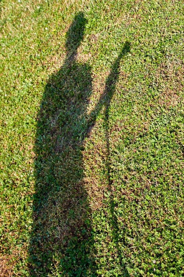 Sombra de un jardinero en el prado imagen de archivo libre de regalías