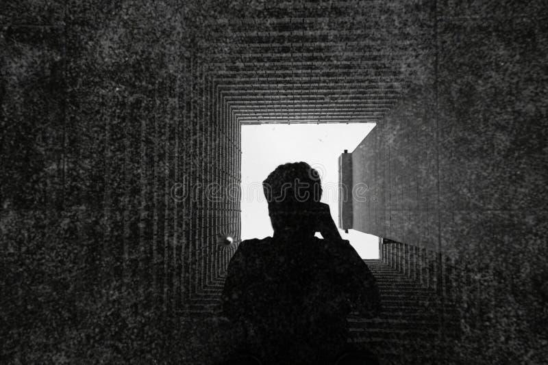 Sombra del hombre mientras que la foto de la toma en refleja de vac?o concreto constructivo abstracto o del t?nel de la fachada c foto de archivo libre de regalías
