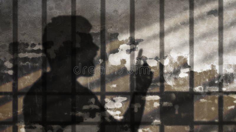 Sombra del hombre que habla debajo de barras de la cárcel fotografía de archivo libre de regalías