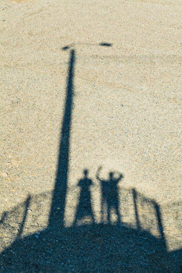 Sombra del hombre y de la mujer en una arena imagen de archivo libre de regalías