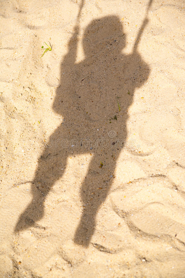 Sombra del niño en el oscilación foto de archivo