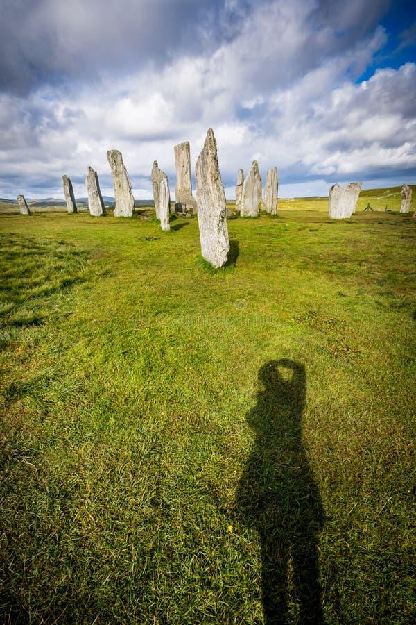 Sombra del ` s del fotógrafo en la hierba delante de las piedras derechas de Callanish imagen de archivo libre de regalías