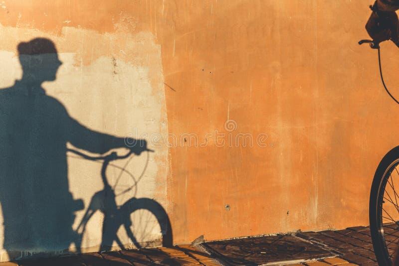 Sombra do ciclista masculino irreconhecível em um estilo de vida rotineiro diário da parede colorida imagens de stock