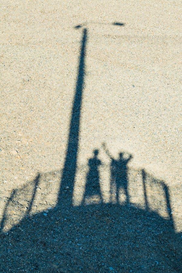 Sombra do homem e da mulher em uma areia imagem de stock