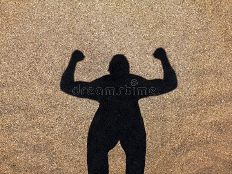 Sombra do homem na praia, silhueta do músculo do homem forte na areia fotografia de stock